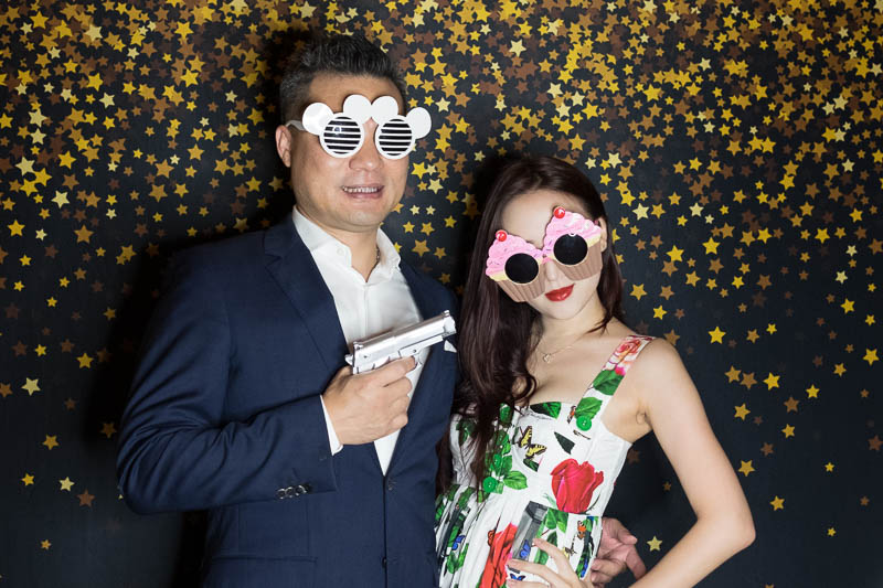 Couple wearing funky glasses at photo booth