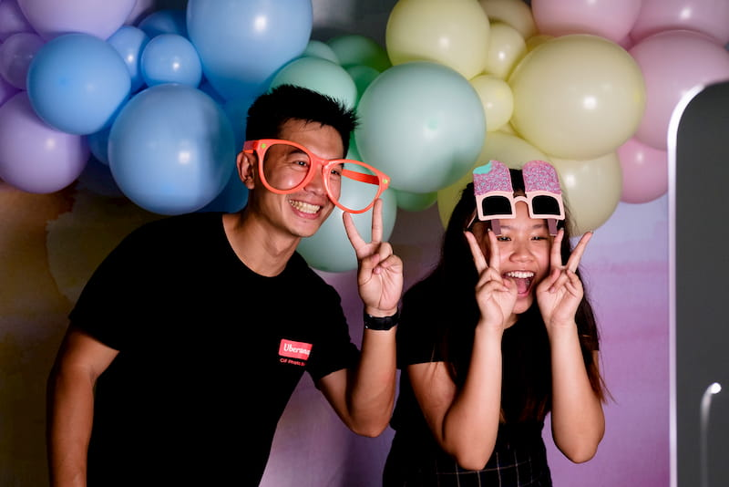 Friends posing at photo booth in front of balloon backdrop