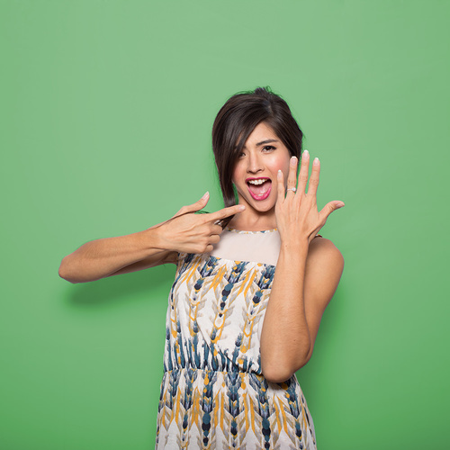 Woman posing with wedding ring at green screen photo booth
