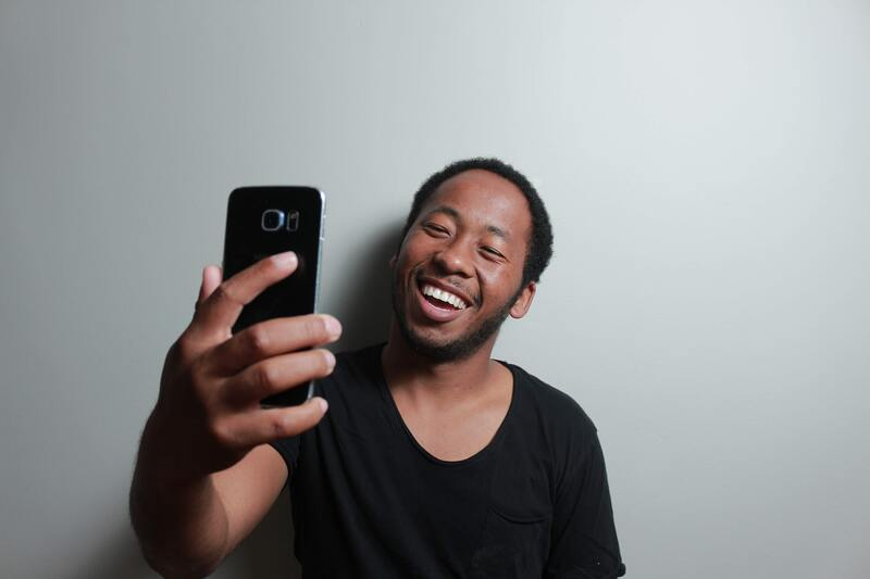 Man taking selfie against white background with virtual photo booth
