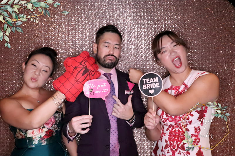 Group of friends posing at wedding photo booth