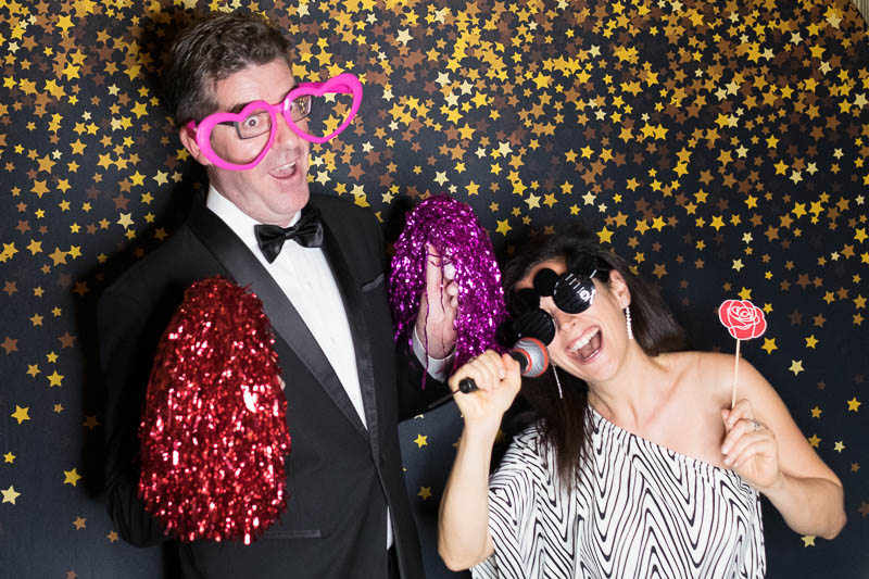 Well dressed couple posing with photo booth props