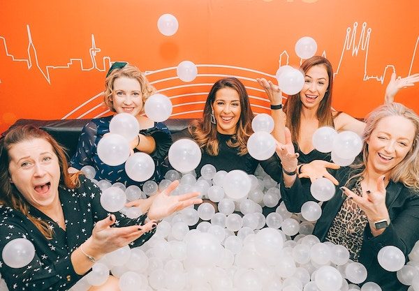 Group of friends having fun at a ball pit photo booth