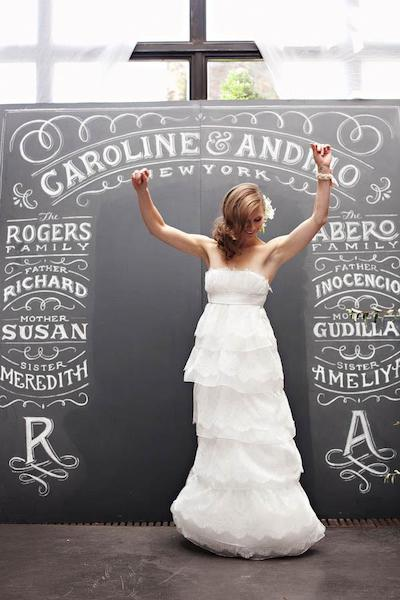 Bride at photo booth with chalkboard backdrop