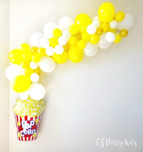 Using a popcorn balloon garland as a photo booth backdrop