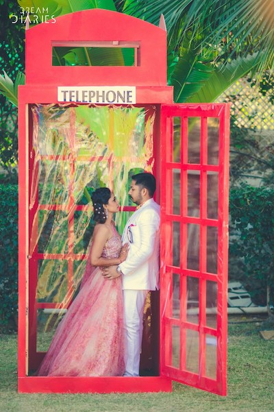 Couple posing at vintage telephone booth photo booth