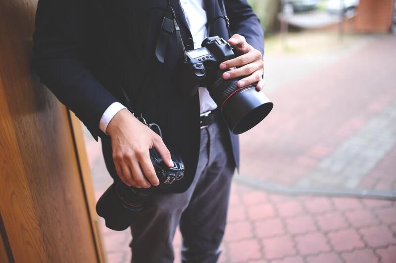 Virtual wedding photographer holding two cameras