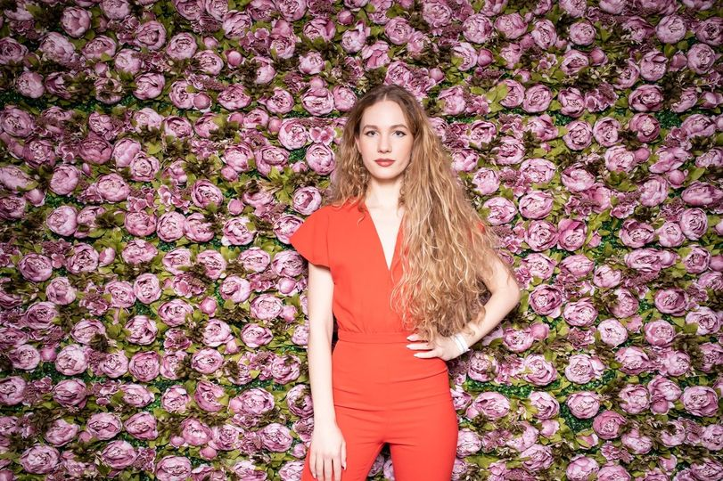 Woman standing flower floral arrangement wall photoshoot photobooth
