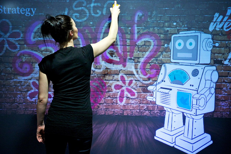 Woman spray-painting on a live grafitti digital wall at event photoshoot photobooth interactive