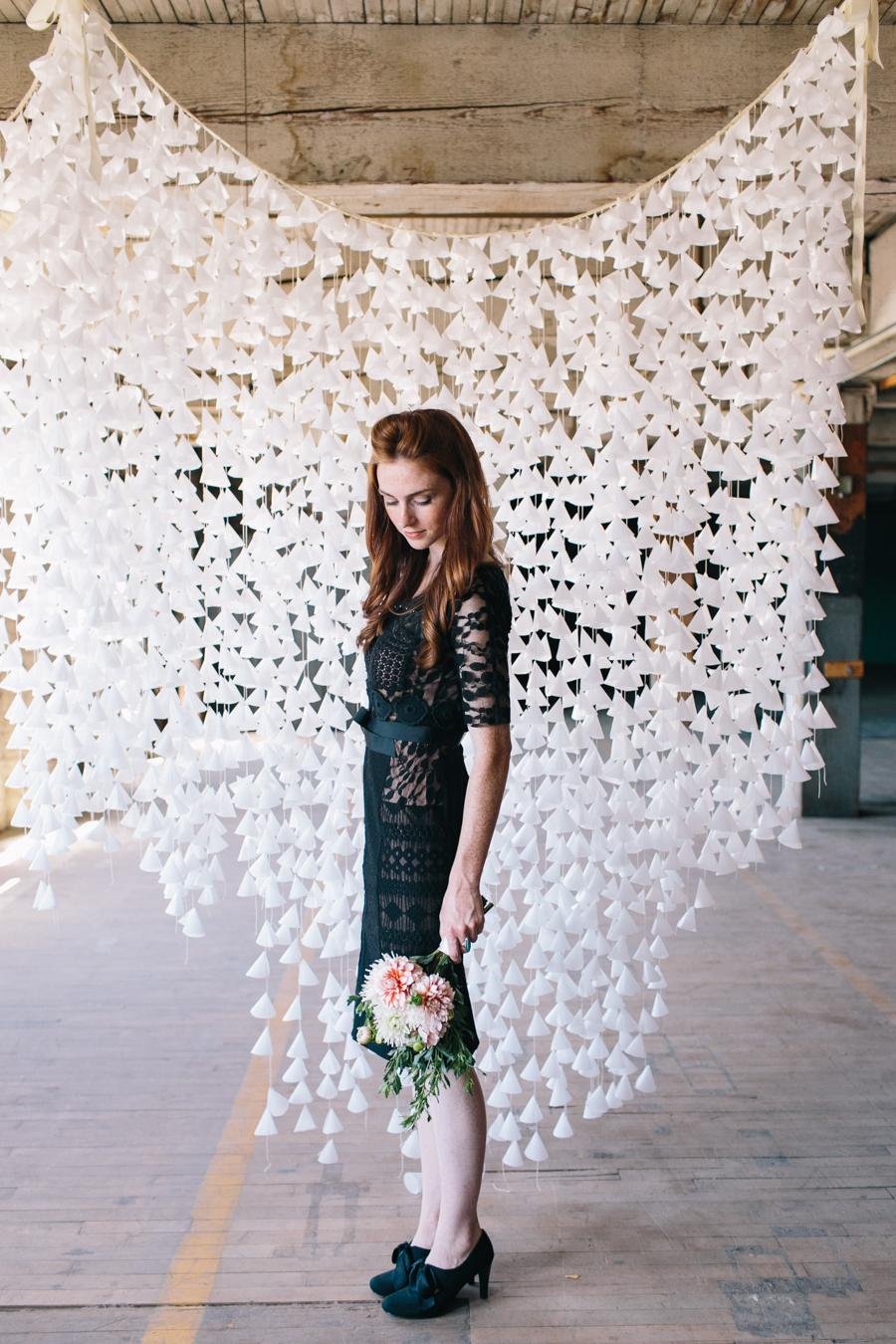 Lady posing with bouquet of flowers against wax paper backdrop in industrial site for photoshoot photobooth wedding contemporary style