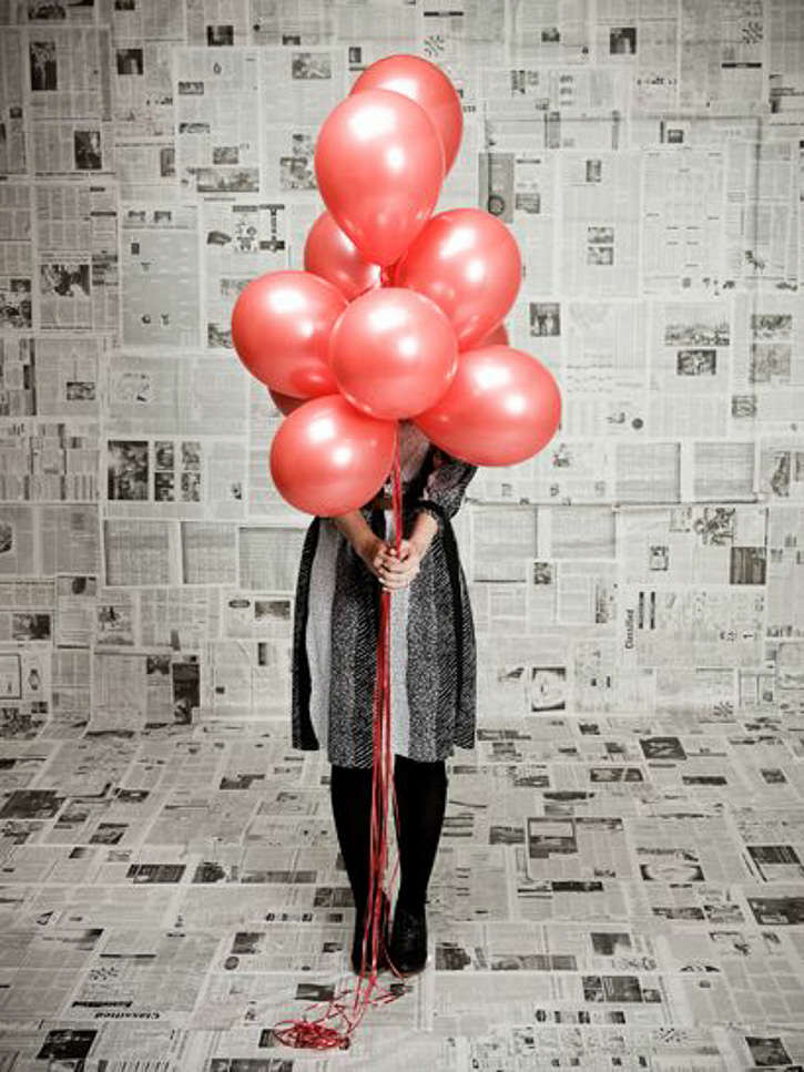 Woman posing with red balloons bunch in newspaper backdrop background for photoshoot photobooth
