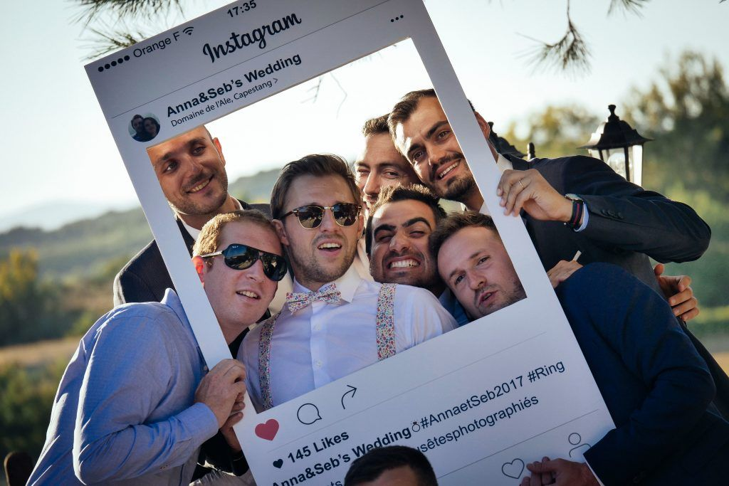 Group of guys posing together with cut-out frame instagram social media photoshoot at wedding photobooth gathering event