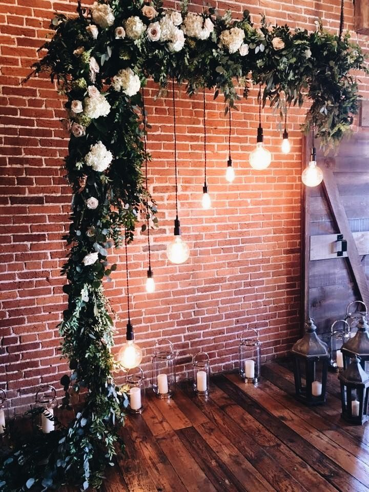 Brick Wall with overhanging frame and light bulbs decorated for wedding event photoshoot photobooth