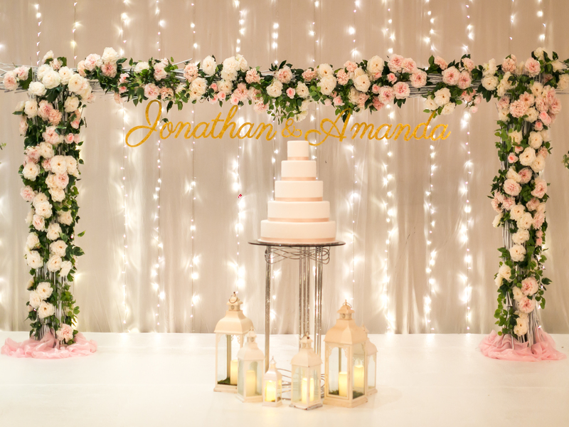 Wedding backdrop fairy lights with flowers and wedding cake for photoshoot photobooth