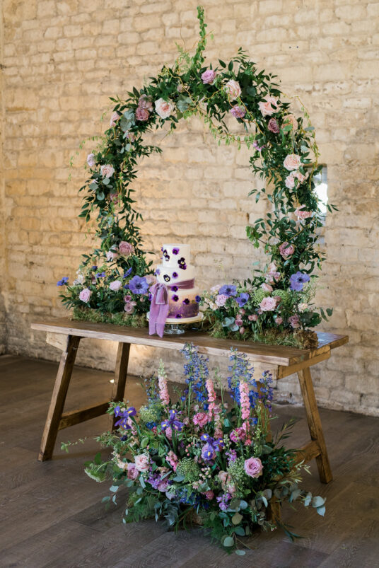 Wreath positioned on table with decorations against brick wall for photoshoot photobooth at wedding venue