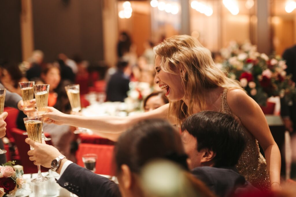 Woman cheering with guests at the dinner table at the wedding reception toasting wedding ceremony photography photograph