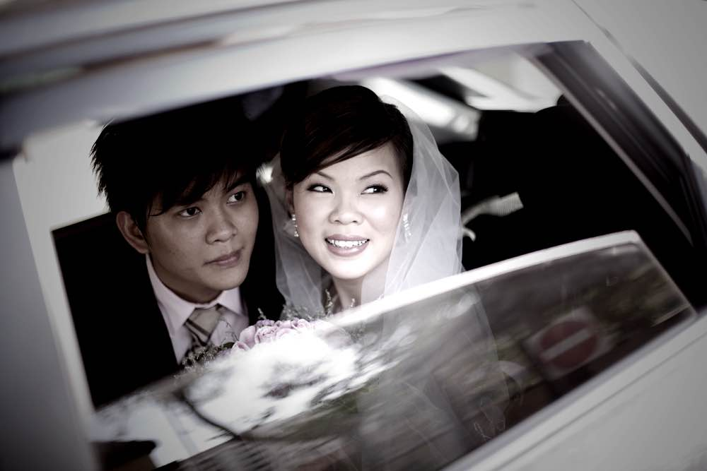 Wedding Couple in their car leaving the wedding ceremony by photographer and photograph