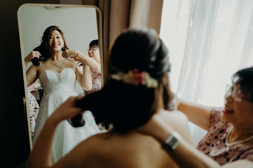 Bride donning on dress with friends and bridesmaids before wedding ceremony photography photoshoot wedding event photographers