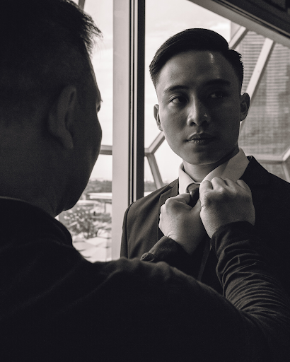 Groom having bow-tie done by friend before wedding photoshoot photography