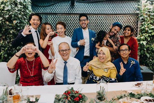 Family having photo together with couple during wedding cohesion photography photograph at wedding venue