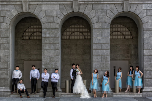 Couple having their photoshoot together outside with groomsmen and bridesmaids outdoor venue photographers and photography event wedding