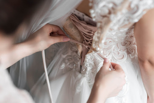 Bride donning on her dress pre-wedding before wedding photoshoot