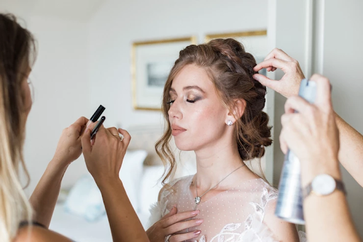 Bride having her makeup being done up by artists before wedding photoshoot