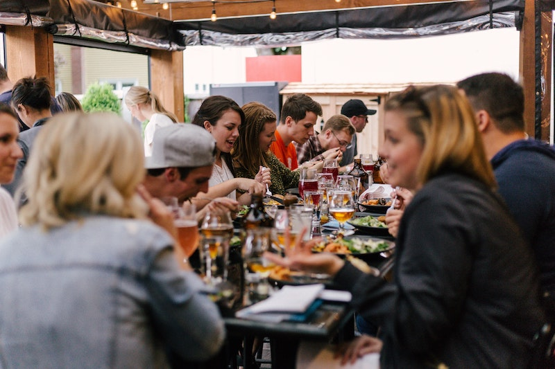 Group of friends eating and talking at a long table