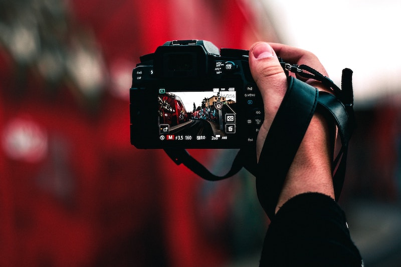Hand holding camera in front of red background