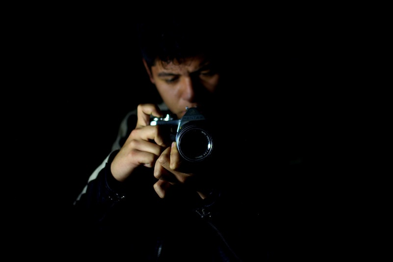 Photographer in front of black background