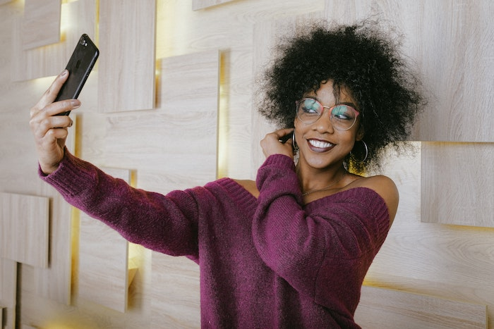 Woman taking selfie with Cosmo virtual photo booth