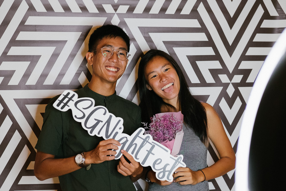 Couple holding props and posing at photo booth
